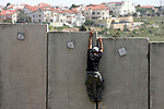 A Palestinian youth climbs the Israeli separation barrier during the weekly demonstration against Israel's separation barrier in the West Bank village of Nilin, near Ramallah, Friday, April 8, 2011. Israel says the barrier is necessary for security while Palestinians call it a land grab. Photo by Issam Rimawi