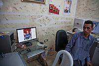 Tunisia, Sidi Bouzid, il dopo rivoluzione. Il fotografo che fece l'ultima foto a Mohamed Bouazizi (l'attivista che si diede fuoco dando inizio alla sommossa in Tunisia) seduto accanto al computer nel suo studio. Appese al muro varie fotografie.<br /> TUNISIA after spring revolution