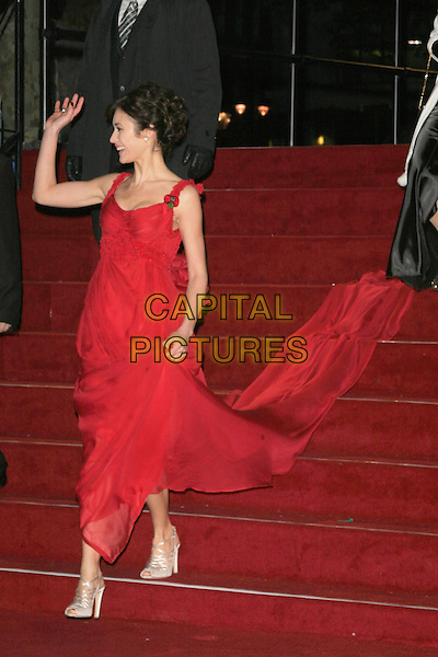 """OLGA KURYLENKO.The Royal World Premiere of """"Quantum Of Solace"""" at the Odeon Leicester Square, London, England..October 29th 2008.James Bond full length red long maxi dress bows ruffles profile train hand waving gold strappy sandals .CAP/AH.©Adam Houghton/Capital Pictures."""