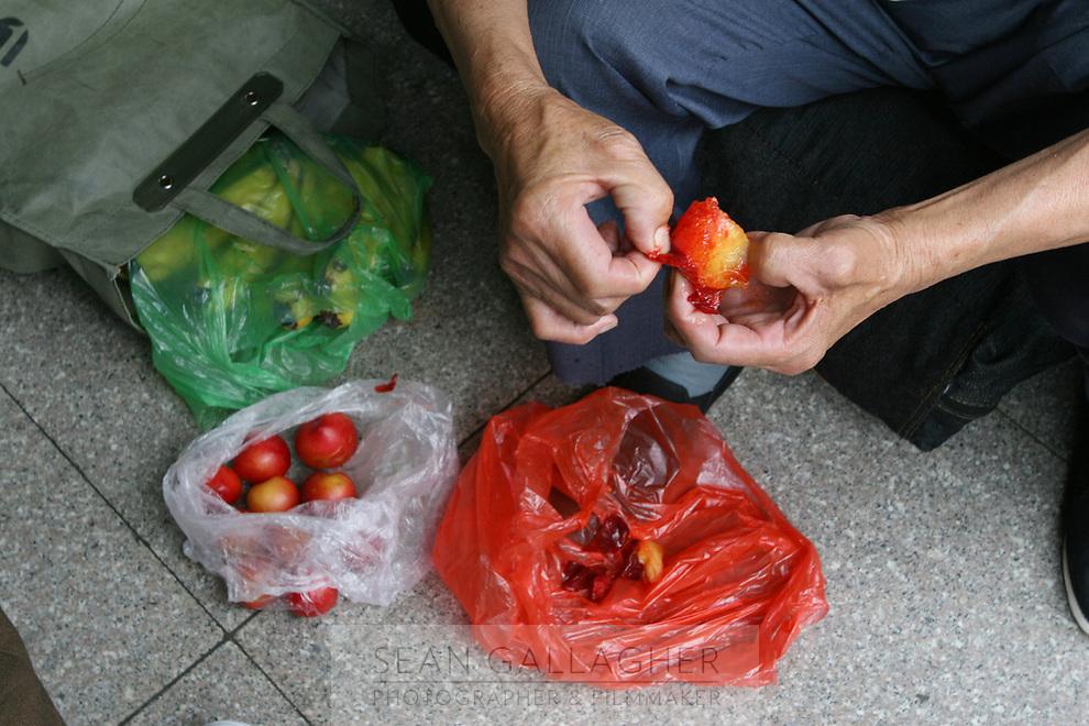 CHINA. Beijing. A man peeling fruit in Beijing West Train Station. 2007.