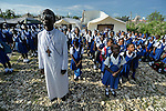 Father Jean-Chenier Dumais, a Russian Orthodox priest in Port-au-Prince, Haiti, stands with children of the Notre Dame de Petits school while they sing the national anthem as Haiti's flag is raised at the beginning of a school day. The school's building collapsed in the January 2010 earthquake, and classes are currently conducted in the large tents in the background, provided by International Orthodox Christian Charities.