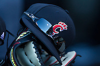 A Cincinnati Bearcats cap sits on top of a glove in the visitors dugout during the game against the Wake Forest Demon Deacons at Wake Forest Baseball Park on February 21, 2014 in Winston-Salem, North Carolina.  The Bearcats defeated the Demon Deacons 5-0.  (Brian Westerholt/Four Seam Images)