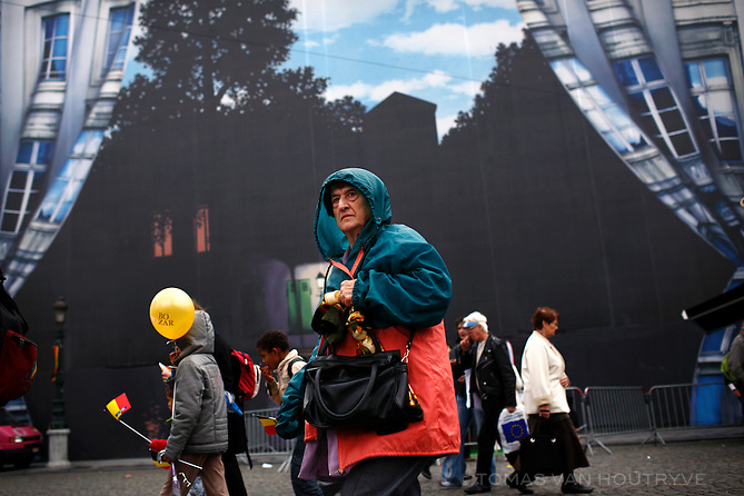 Belgians gathering for the National Independence Day parade pass a large scaffolding cover with images inspired by Belgian surrealist painter René Magritte in Brussels, Belgium on 21 July, 2008. Disagreements between the Flemish and French speaking populations of Belgium have lead to the worst government crisis since the nation's founding.