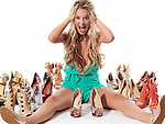 Young woman can't find a pair of matching shoes, witting on the floor screaming surrounded by several pairs of different fashionable shoes isolated on white background. Humorous concept. Image © MaximImages, License at https://www.maximimages.com