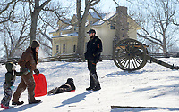Andrew (right) and Nancy Newton of Prairie Grove prepare their daughter, Abi Newton, 5, (left) and son, Gabe Newton, 9, for another trip downhill Friday, Feb. 19, 2021, while sledding near a Civil War-era cannon at Battlefield State Park in Prairie Grove. The Newtons were taking a break from virtual instruction to take advantage of the good sledding conditions before warm temperatures melted the snow from the hillside. Visit nwaonline.com/210220Daily/ for today's photo gallery. <br /> (NWA Democrat-Gazette/Andy Shupe)