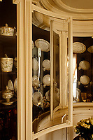 The curved doors of the built-in cabinet in the games room protects Sevres and Vieux Paris dinner services