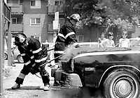 June, 1983 file photo - Montreal, Quebec, CANADA - Firemen at work on a car in fire
