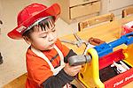 Education Preschool boy wearing dressup fire hat using toy tool kit