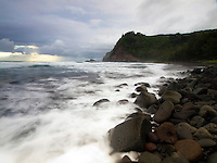 Waves rush onto the rocky shoreline of Pololu Valley's beach in the morning light, Hawi, Big Island.