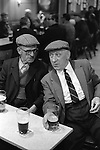 Two men friends drinking together, Saturday night at Byker & St.Peters Working Men's Social Club Newcastle upon Tyne, Tyne and Wear northern England 1973. Typically they wear tweed flat caps.