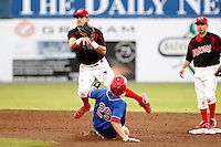 Batavia Muckdogs second baseman Jeremy Patton #12 turns a double play as Caleb Ramsey #29 slides in during a game against the Auburn Doubledays at Dwyer Stadium on August 27, 2011 in Batavia, New York.  Vance Albitz is in back as Batavia defeated Auburn 7-5.  (Mike Janes/Four Seam Images)