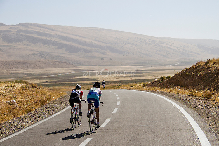 SULAIMANIYAH, IRAQ: Professional cyclist Nyan Yassin (left) takes part in individual time trials during a competition in Sulaimaniyah.  Here she is overtaking a competitor who had a four minute head start on her.<br /> <br /> Nyan Yassin, 24, is a professional competitive cyclist in Sulaimaniyah in the semi-autonomous region of Iraqi Kurdistan.  She is the captain of an all-female club called Newroz Club, which is the only cycling club for women in Sulaimaniyah, although there are other clubs around Iraq.  She trains and competes on roads that are badly surfaced and busy with traffic.<br /> <br /> Nyan was the first woman to start cycling in Sulaimaniyah.  She was always competitive and after trying her hand at different sports she settled on cycling.  She is now the top female cyclist in Iraq.  Her nickname is MigMig after the noise made by the cartoon character Roadrunner.<br /> <br /> Despite being clearly talented at her sport Nyan knows that in a couple of years she will have to get married and then abandon it as, in the traditional society that Kurdistan is, being a wife and a competitive sportswoman at the same time is not an option.<br /> <br /> Photo by Gona Hassan/Metrography