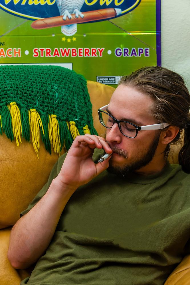 Young people smoking marijuana and relaxing at home