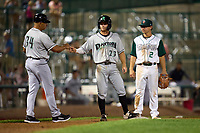Dayton Dragons Matt McLain (23) fist bumps manager Jose Moreno (34) as third baseman third baseman Zack Mathis (2) looks on during a game against the Fort Wayne TinCaps on August 27, 2021 at Parkview Field in Fort Wayne, Indiana.  (Mike Janes/Four Seam Images)
