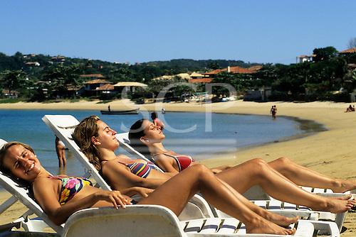 Buzios, Brazil. Three girls in bikinis relaxing on sun loungers on Ferradura beach.