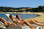 Buzios, Brazil. Three girls in bikinis relaxing on sun loungers on Ferradura beach.