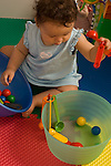 9 month old baby girl sitting playing with measurings spoons, balls, and bowls