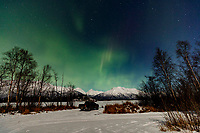 Winter landscape of people viewing the Aurora Borealis / Northern Lights from inside their pickup truck vehicle over the Chugach Mountains and frozen Knik River in Southcentral, Alaska<br /> <br /> Photo by Jeff Schultz/  (C) 2021  ALL RIGHTS RESERVED