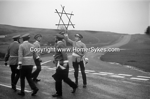 Goathland Plough Stots. Goathland Yorkshire UK  Sword Dance Team 1972.<br /> <br /> This interesting custom would not exist if it had not been revived by F. W. Dowson in 1923 after a lapse of nearly sixty years. Apart from a break in the second world war, the custom has carried on since then. The traditional date for its performance was plough Monday, or first Monday after Twelfth Night (6 January), which by tradition was the first day of the agricultural labourers' week's holiday. However, after 1947 this day was changed to the first Saturday after plough Monday. In northern Middle English 'stot' meant a bullock, but the word has been transferred to the youths who drag a bullock about in the Plough Monday procession. According to the traditional custom this was led by a 'Lord' and 'Lady' followed by a group of men in disguise, known as 'Toms', who made a collection. Next came the sword-dancers and musicians and taking up the rear<br /> were the plough stots, with 'Betty' carrying a broom, and 'Old Isaac' collecting alms. The whole procession could number as many as forty people. During the week's holiday they first toured their own village and then the ones near by, especially those that had no team. At various places in each village the sword-dancers performed and a collection was made. Donations were expected and if they were not forthcoming the farmer ran the risk of having his lawn ploughed up. At the end of the week it was the custom to hold a festival and dance, to which the women folk were invited. Expenses were met out of the funds collected during the week and the remaining money divided up between the performers.