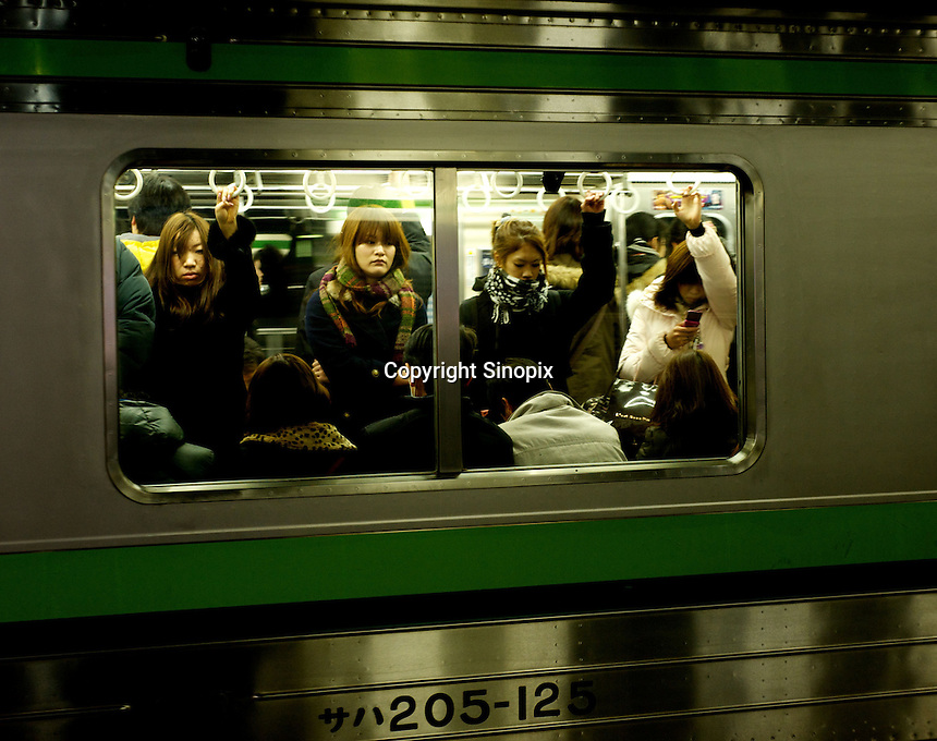 Returning home on a commuter train in Yokohama, Japan.