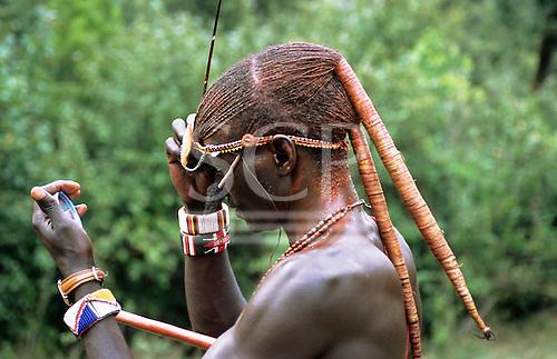 Lolgorian, Kenya. Portrait of a Maasai moran warrior using a mirror to prepare for the Eunoto.