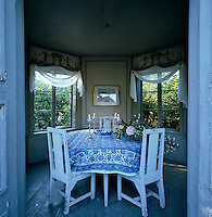 A summer dining room is housed in an octagonal summer house furnished with simple white painted dining chairs and round table