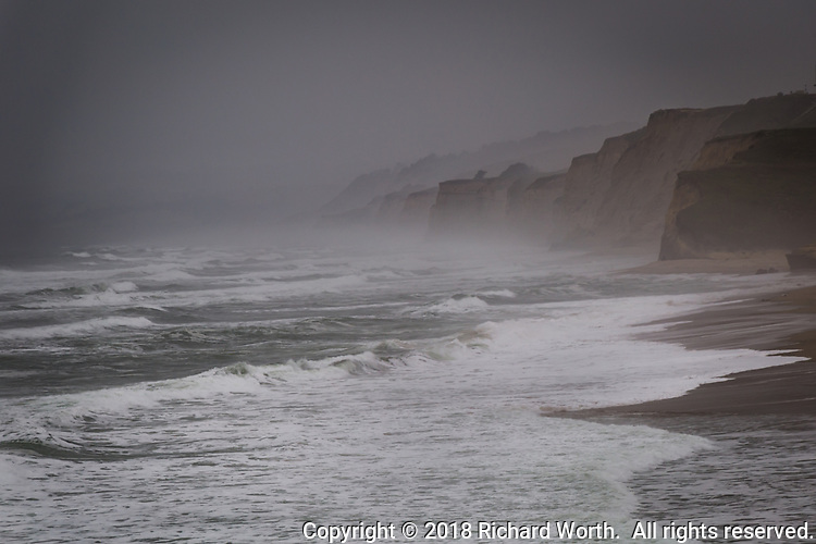 A veil of fog over bluffs along the Pacific coast south of San Francisco.