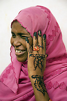 """Djibouti. Djibouti province. Djibouti. """"Oui à la vie"""" (Yes to life) was the first djiboutian association for seropositive people living with the HIV Aids disease. Seropositive smiling muslim woman displays newly applied Henna on her hand.Temporary tattoos. Hijab on her head, Gold tooth. The Global Fund through the djiboutian Ministry of Health supports the programm with an Aids grant (financial aid).  © 2006 Didier Ruef"""