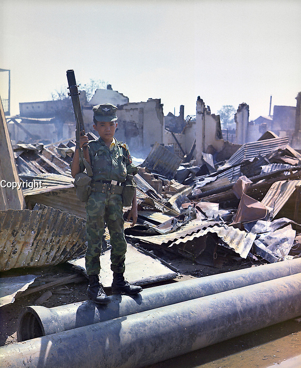 """Tan Son Nhut, Vietnam. 05/07/1968 -  This twelve year old ARVN Airborne trooper with M-79 grenade launcher accompanied the Airborne Task Force Unit on a sweep through the devastated area surrounding the French National Cemetery on Plantation Road after a day long battle there. The young soldier has been """"adopted"""" by the Airborne Division."""
