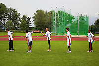 Switzerland. Canton Ticino. Tenero. Centro Sportivo Nazionale della Gioventù - Tenero (CST). Nationales Jugendsportzentrum Tenero. From left to right: Bastien Mouthon, Killian Imwinkelried, Alain Enz, Lucio Romero and Yanier Bello are training  under the rain. The 4 × 100 metres relay or sprint relay is an athletics track event run in lanes over one lap of the track with four runners completing 100 meters each. A relay baton is carried by each runner and must be passed within a 20 m changeover box (usually marked by yellow lines) which extends 10 m on either side of each 100 m mark of the race. 31.05.11 © 2011 Didier Ruef