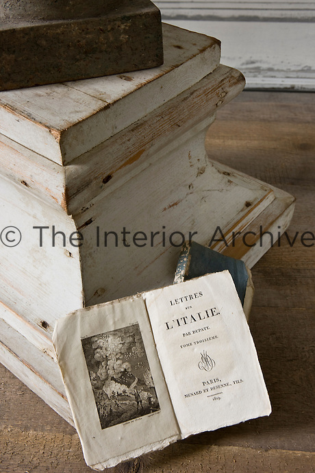 An open 19th century book is propped against the wooden plinth supporting a metal urn on a side table in the salon