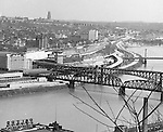 Pittsburgh:  View of Duquesne University and bluff from Mt. Washington.  View also includes Railroad bridge, Liberty Bridge, Try Street Terminal and University of Pittsburgh in the background.