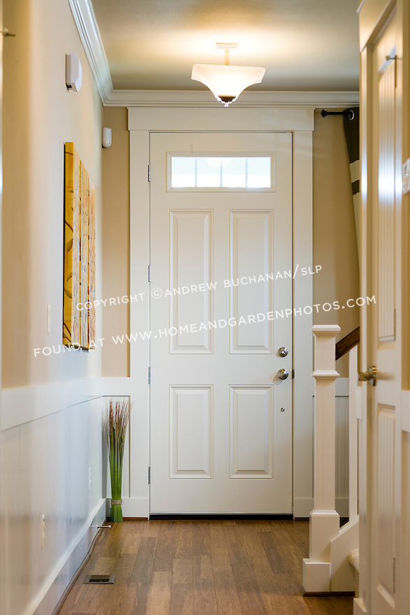 An image of the inside view of a white, overheight front door with window panes at the top, a newel post and banister coming from upstairs, and hardwood floors below.