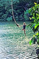 Young girl jumping off rope swing at Green lake, Big Island of Hawaii