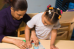 Education Preschool 3-4 year olds female teacher helping girl by steadying puzzle horizontal