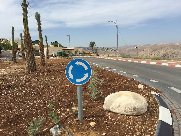 """14. """"Roundabout"""": median and highway, Nofei Prat, West Bank.<br /> <br /> The bright blue """"roundabout"""" sign seems like a metaphor for the ongoing land disputes in the West Bank. Many settlers use the biblical terms, """"Judea and Samaria,"""" to refer to the area in place of """"West Bank."""" Does this help justify their presence and their actions? On the left one can see the settlers' homes; on the right the Judean Desert hills and another settlement in the distance. And in the middle, the blue sign and a heavy rock are firmly planted, as if to say, """"We're not going anywhere!"""""""