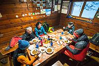 A ski tour through the Pirin Mountains of Bulgaria. Inside the Tevno Ezero Hut a group of skiers eat dinner.