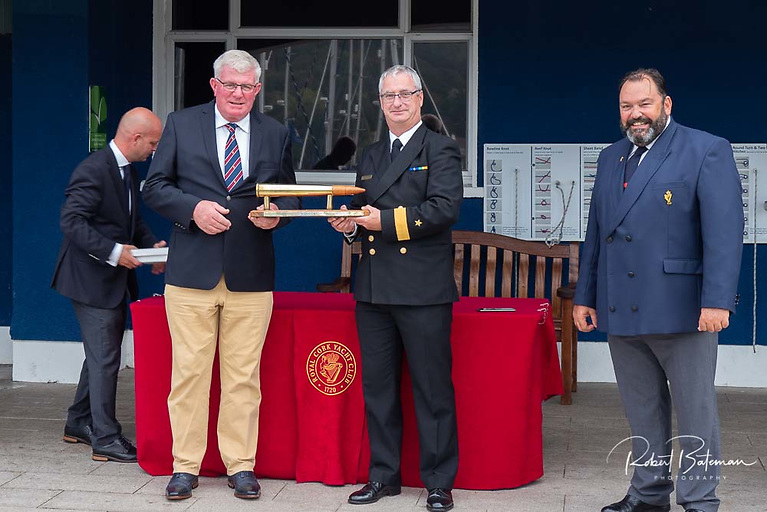 """Commodore Michael Malone Flag Officer commanding the Naval Service presents the winning Trophy to Denis Murphy of """"Nieulargo""""  watched by Colin Morehead  Admiral Royal Cork Yacht Club"""