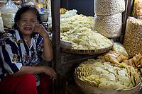 Yogyakarta, Java, Indonesia.  Woman Selling Nuts, Melinjo Fruit Chips, and Snacks, Beringharjo Market.