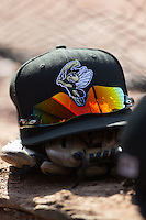 A Savannah Sand Gnats hat sits on top of a glove in the visitor's dugout during the game against the Hickory Crawdads at L.P. Frans Stadium on June 14, 2015 in Hickory, North Carolina.  The Crawdads defeated the Sand Gnats 8-1.  (Brian Westerholt/Four Seam Images)