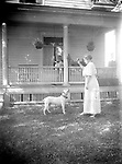 PLAYING FETCH. A white pit bull terrier waits attentively for his lady to throw his ball. The dog looks similar to the pet on LB019 and LB021, but in this image the pet's people are white. The man of the house, partially hidden by the porch column, is looking over the scene from the porch swing, smoking his cigar.<br /> <br /> Photographs taken on black and white glass negatives by African American photographer(s) John Johnson and Earl McWilliams from 1910 to 1925 in Lincoln, Nebraska. Douglas Keister has 280 5x7 glass negatives taken by these photographers. Larger scans available on request.
