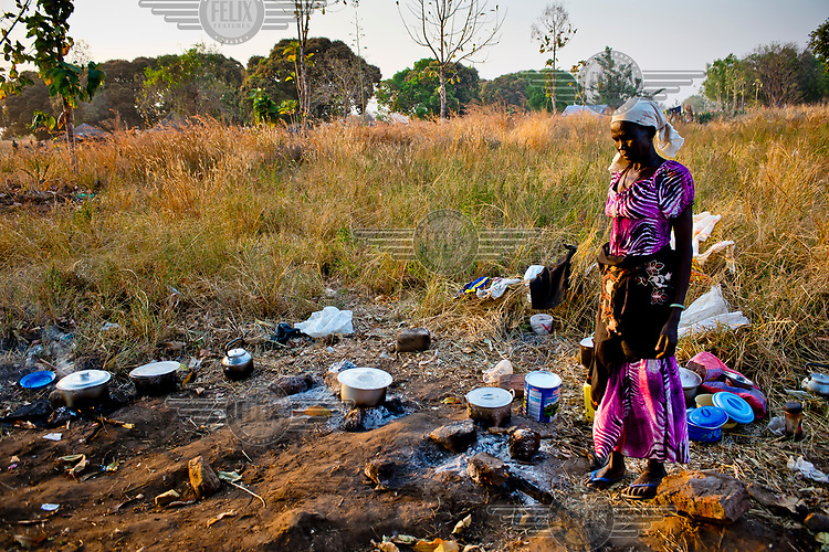 A South Sudanese refugee checks her pots in an area used for cooking at the Dzaipi transit centre.