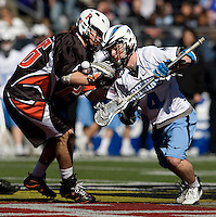 Matt Dolente (4) of Johns Hopkins has the ball checked away from him by Chris Chandler (16) of Princeton during the Face-Off Classic in at M&T Stadium in Baltimore, MD