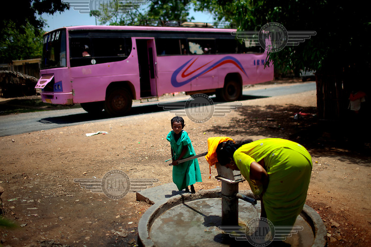 A bus drives past as a tribal woman and young girl pump water from a well in the remote village of Chingawarm. A bus owned by the same company and traveling the same road was destroyed three kilometers from here by a Indian Maoist insurgents, known as Naxals or Naxalites, using an improvised explosive device on 17 May 2010. /Felix Features