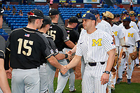 Michigan Wolverines head coach Erik Bakich (23) shakes hands with Rob Regine (15) after a game against Army West Point on February 18, 2018 at Tradition Field in St. Lucie, Florida.  Michigan defeated Army 7-3.  (Mike Janes/Four Seam Images)