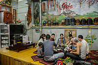 Customers at the Ly-Ly 1-2 restaurant sit around a low table eating the house speciality, a traditional Vietnamese dish made with horse meat known as 'Than Co Ngua'. The dish uses black cardamom (Thao Qua) as one of its key ingredients.