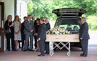 """Pictured: Rachel Stewart (L) and Eve Stewart (2ndL) who wears a spotty dress, the daughter and granddaughter of Pat Stewart are joined by close family and relatives stand as the coffin of Pat Stewart arrives<br /> Re: The funeral of Pat Stewart at the Cardiff and Glamorgan Memorial Park and Crematorium, Wales, UK. Pat Stewart became famous as """"the girl in the spotty dress"""" after an iconic image taken by Bert Hardy in Blackpool in 1951."""
