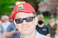 """A man wears a hat depicting a bat that reads """"Wuhan Wild Wings"""" as people gather for an anti-lockdown protest organized by the alt-right group Super Happy Fun America near the home of Massachusetts governor Charlie Baker in Swampscott, Massachusetts, on Sat., May 16, 2020. The hat is referring to Wuhan, China, the origin of the COVID-19 coronavirus pandemic, and is similar to racist references to the virus among some conservative circles as Kung Flu or China Virus. The protest was in defiance of Massachusetts orders mandating face coverings and social distancing and prohibiting gatherings larger than 10 people during the ongoing Coronavirus (COVID-19) global pandemic. The state's stay-at-home order is expected to be updated on May 18, 2020, with a phased reopening plan issued by the governor as COVID-19 cases continue to decrease. Anti-lockdown protests such as this have become a conservative cause and have been celebrated by US president Donald Trump. Many of the protestors displayed pro-Trump messages or wore Trump campaign hats and shirts with phrases including """"Trump 2020"""" and """"Keep America Great."""" Super Happy Fun America, organizers of the protest, are an alt-right organization best known for creating the 2019 Boston Straight Pride Parade."""