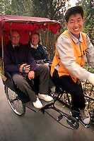 Rickshaw driver with tourists in Beijing China.