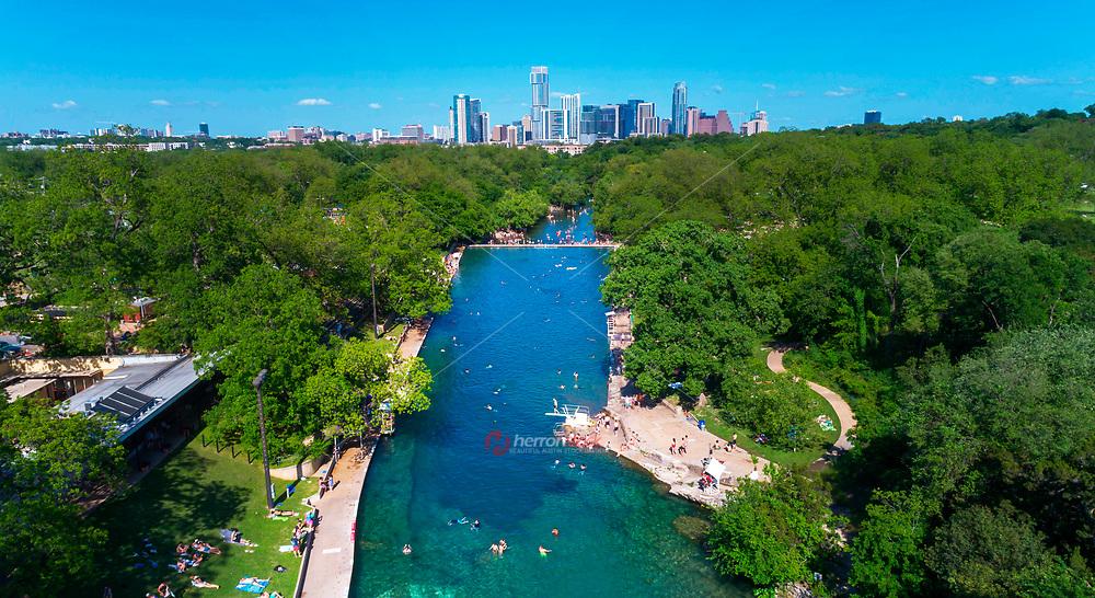 La piscina Barton Springs es conocida como la joya de Austin. Desde lo alto de esta imagen aérea tomada desde un dron, se puede ver las aguas cristalinas y verde esmeralda de la piscina Barton Springs, en el primer plano Barton Creek, un abrevadero gratuito para aquellos que les gusta traer sus perros o tomarse unas cuantas cervezas o encender un cigarillo y evitar el horrible calor del verano de Austin, y el majestuoso horizonte de Austin que se alza sobre el Zilker Metropolitan Park.